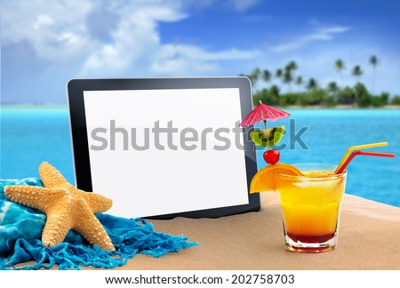 tablet, sea star and tropical cocktail in the sand - stock photo