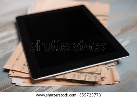 Tablet sitting on top of newspapers - stock photo