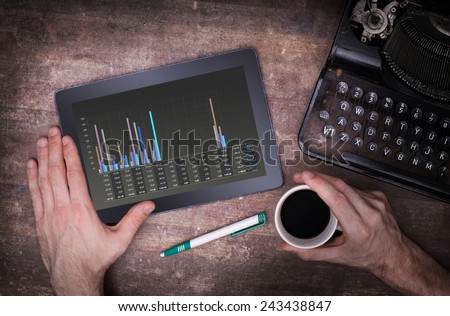 Tablet touch computer gadget on wooden table, graph, vintage look - stock photo