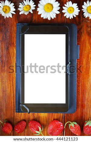 Tablet with a white screen lies on the wooden background with fresh strawberries and chamomiles - stock photo