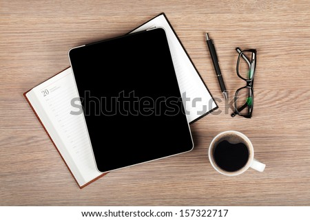 Tablet with blank screen and coffee cup on office wooden table - stock photo