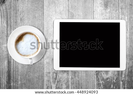 Tablet with blank screen and coffee on wooden table with view from above - stock photo