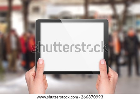 Tablet with blank screen in hand on background of street - stock photo