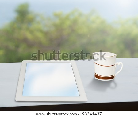 tablet with coffee mug on table with nature view outside - stock photo