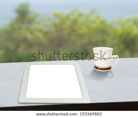 Tablet with cup of coffee on table with nature view outside - stock photo