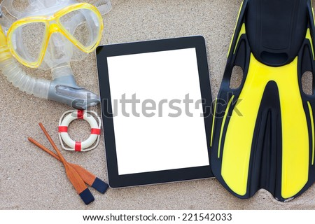 tablet with isolated screen on the sand with fins and snorkel - stock photo