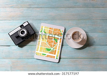 Tablet with map gps navigation application, camera and cup of coffee on wooden background - stock photo