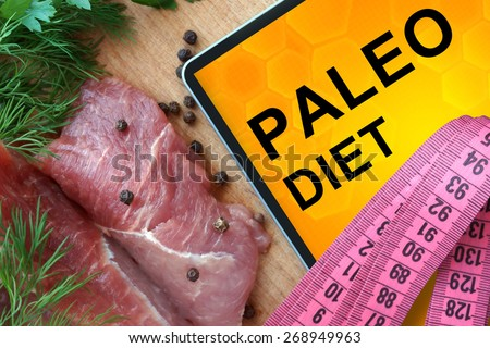 Tablet with Paleo diet and Fresh Meat  on Wooden Board   - stock photo