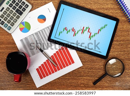 tablet with stock graph on wooden table - stock photo