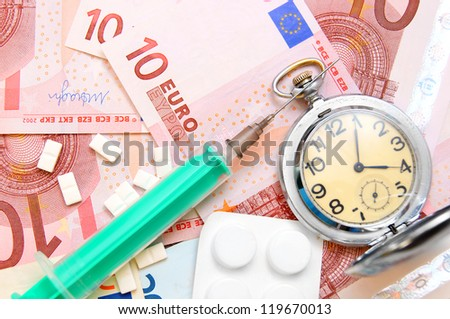 Tablets, a syringe and an watch on money. - stock photo