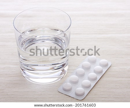 tablets an a glass of water - stock photo