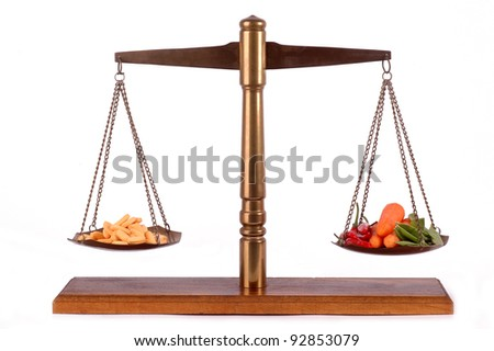 Tablets and fresh vegetables on a brass scale - stock photo