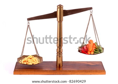 Tablets and fresh vegetables on a isolated scale - stock photo