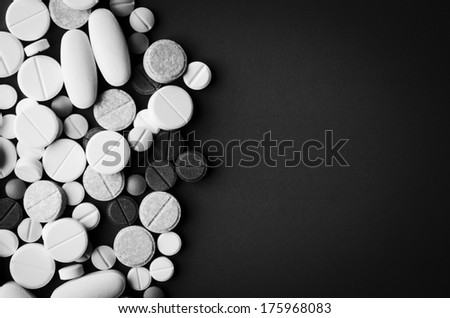 tablets and pills on dark background - stock photo