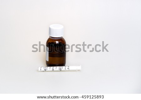 Tablets, cough syrup with a measured syringe, dressing on the face, a thermometer on a white background. Proceeds from the common cold and flu. - stock photo