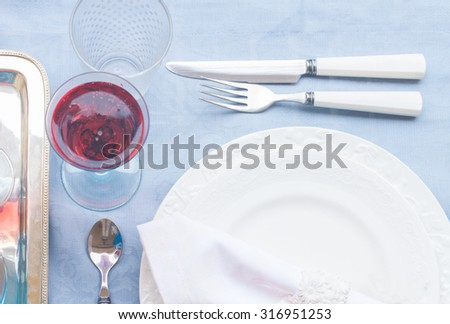 Tableware for dinner with set of plates, cutlery and champagne close up - stock photo