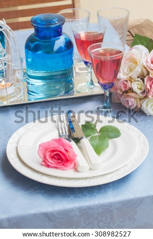 Tableware for dinner with st of plates, cutlery and flowers - stock photo