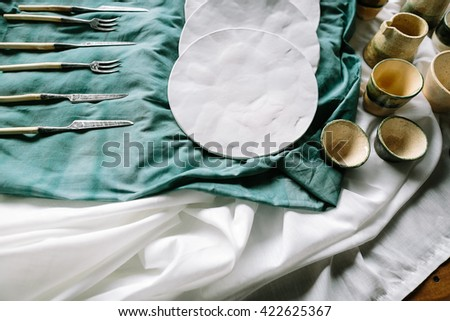 Tableware on a blue background. Tableware on fabric. Knife and forks on fabric. White plates on fabric. Cups and drinking bowls. Tableware on a wooden table. Ware set. Preparation for table layout. - stock photo