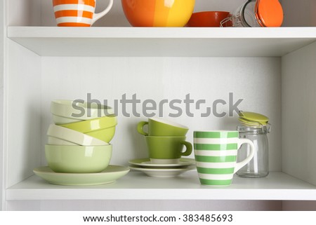 Tableware on shelves in the kitchen cupboard - stock photo