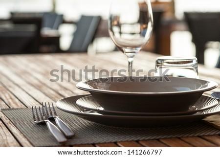 Tableware on teak wood in an italian restaurant. - stock photo