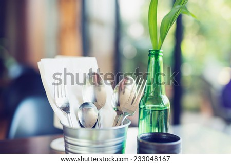 Tablewares in steel can on dinning table - stock photo