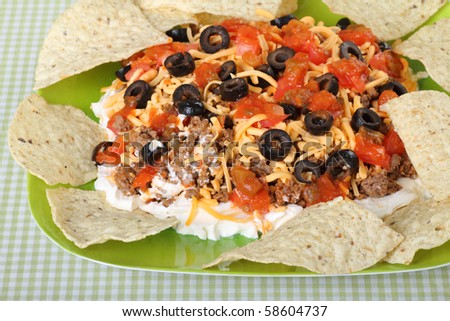 Taco dip with tortilla chips on a plate - stock photo