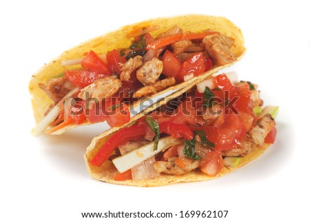 Taco shells filled with grilled chicken meat and fresh vegetable salad - stock photo