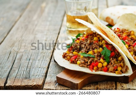 tacos with meat, corn and peppers on a dark wood background. tinting. selective focus - stock photo