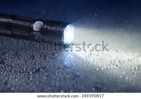 Tactical waterproof flashlight - stock photo