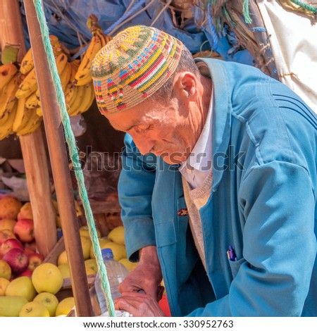 TADDERT, MOROCCO, APRIL 15, 2015: Portrait of local man in traditional headgear prepares orange juice on street stand - stock photo