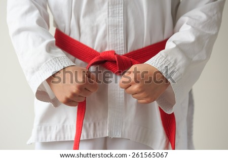Taekwon-do woman tying her red belt and getting ready for training. - stock photo