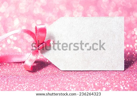 tag with pink ribbon in glitter defocused background - stock photo