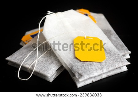 Tagged teabags with string on black surface. - stock photo