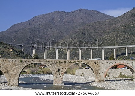Taggia - medieval arched bridge and a modern highway bridge - stock photo