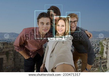 Tagging and sharing a friend in a selfie of four people using facial recogintion software applications in front of a large city for sharing on varous social media platforms - stock photo