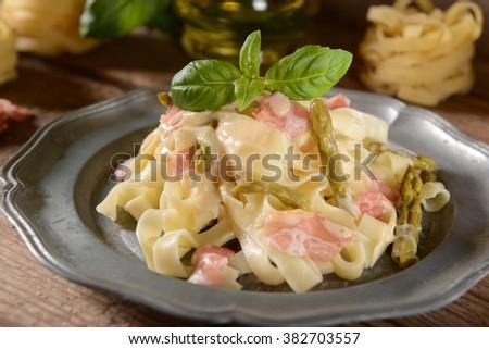 Tagiatelle pasta with asparagus and prosciutto ham - stock photo