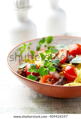 Tagliatelle pasta with beef strips and cherry tomatoes  - stock photo