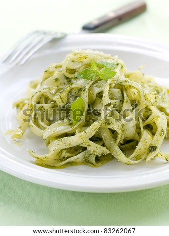 Tagliatelle pasta with pesto on light plate. Selective focus - stock photo