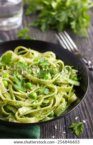 Tagliatelle pasta with spinach and green peas pesto, selective focus - stock photo