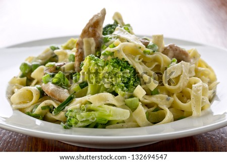 tagliatelle pasta with spring vegetables and grilled chicken - stock photo