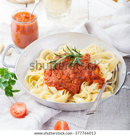 Tagliatelle pasta with tomato sauce and red pesto Italian cuisine - stock photo