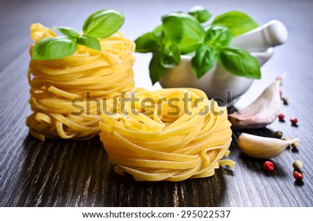 Tagliatelle yellow in dry form in the shape of a nest on a dark background - stock photo