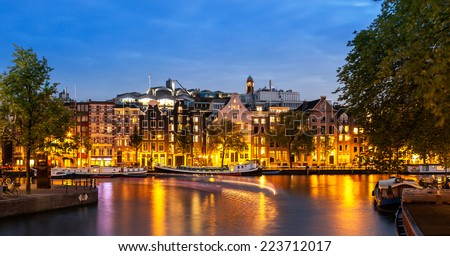 Tail lights of boats crossing canals of Amsterdam at dusk time and apartments illuminated by street lights. - stock photo