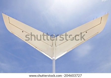 Tail of a modern private jet airplaneon a  with a blue sky - stock photo