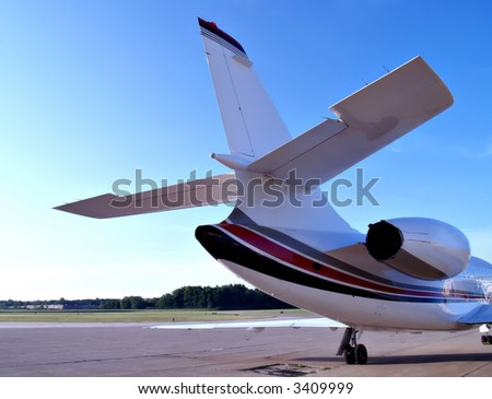 Tail view of a medium sized business jet sitting on the tarmac of a small airport - stock photo