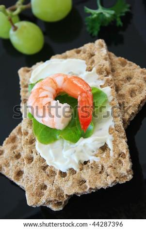 Tailed Prawn on a Rye Bread Cracker - stock photo