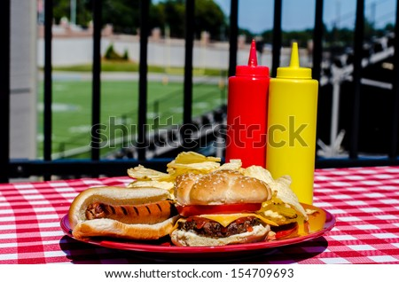 Tailgate party with cheeseburger, hot dog, potato chips and mustard and ketchup bottles.  Football field in background. - stock photo