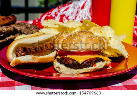 Tailgate party with cheeseburger, hot dog, potato chips, pom poms, hamburger patties, hot dog wieners,  and mustard and ketchup bottles.   - stock photo