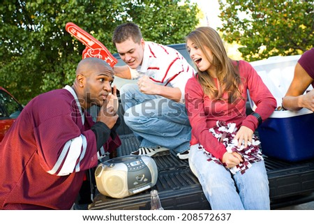 Tailgating: Group Of Fan Friends Listening To Game On Radio - stock photo