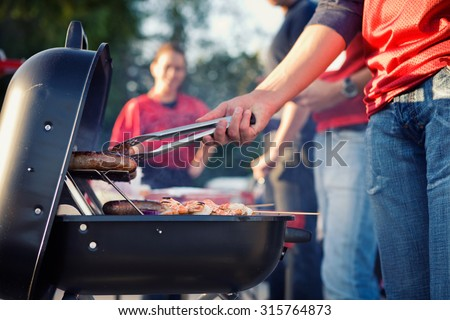 Tailgating: Man Grilling Sausages And Other Food For Tailgate Party - stock photo